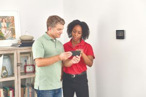 technician showing a thermostat