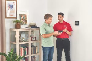 HVAC technician showing thermostat